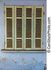 The old window with blue closed shutters on an old house....