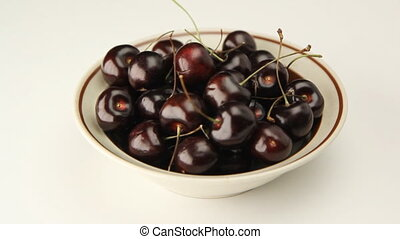 Bowl of Cherries. - Bowl of cherries rotating on a light...