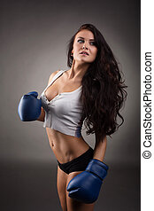 Studio shot of sexy female boxer, on gray background