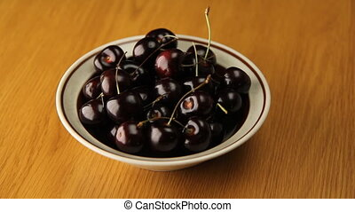 Bowl of Cherries. - Bowl of cherries rotating on wood grain...