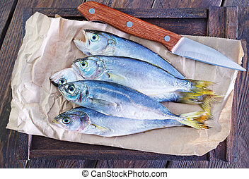 raw fish on paper and on wooden board