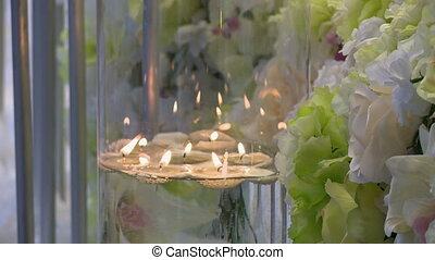 View of melted candles in glass vase with flowers