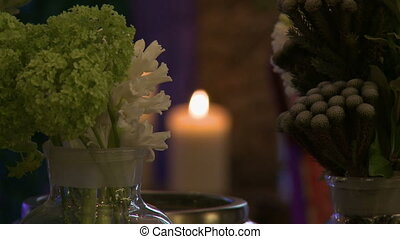Fresh cut flowers on background of lighted candle, close-up