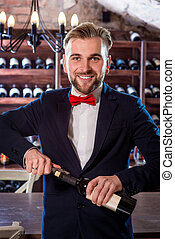 Sommelier in the wine cellar - Sommelier opening wine bottle...
