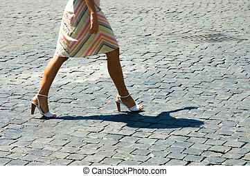 Woman walking on cobblestone - Woman legs walking on...