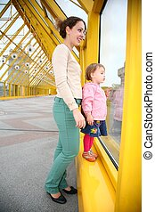 young woman with baby on pedestrain bridge