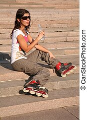 girl-roller sits on the stairs with the bottle of the water