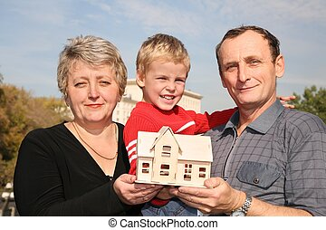grandmother and grandfather with grandson and model of the house