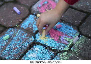 young girl draws with the colourful chalks on the road -...