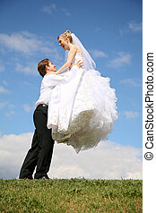 fiance raises bride on the hands on to the meadow