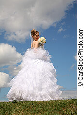 bride stands with the bouquet on to meadow against the background of the sky