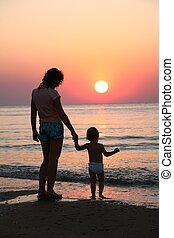 Mummy with baby on sunset at sea