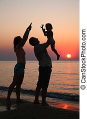 Mummy with daughter and grandfather on sunset ashore
