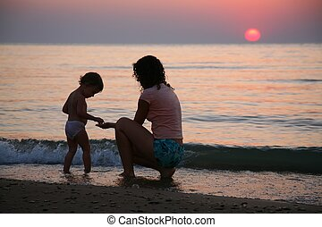 Mummy with the child ashore of sea on sunset