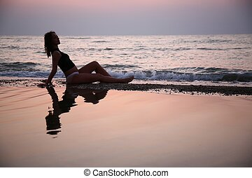 Young woman seats in water on beach on sunset