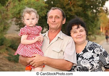 Grandfather with granddaughter on hands and by grandmother