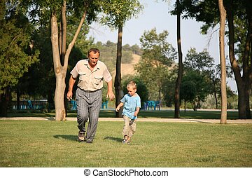 Grandfather with grandson run as to lawn