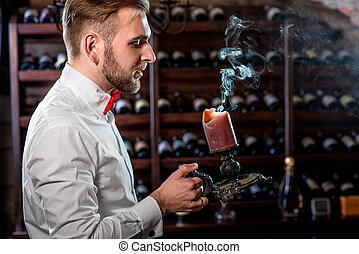 Sommelier in the wine cellar - Sommelier snuffing out candle...