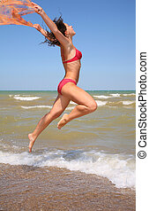 The woman jumps with a scarf
