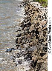 Rock Seawall with Wood Pier in Distance - A rock seawall on...