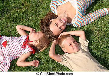mother and children lie on the grass