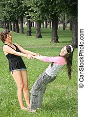 mother and daughter stand on the grass in park