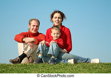 family sits on to the meadow