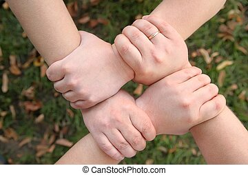 four hands hold each other