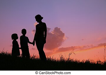 silhouette mother with children on sunset