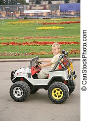 boy in toy car in park