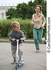 mother runs after the son on the bicycle