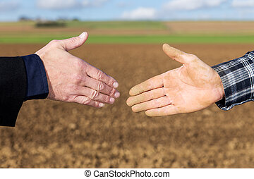 Handshake between businessman and farmer - Close up...