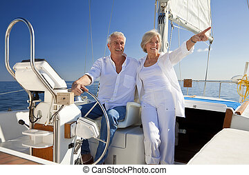 Happy Senior Couple At The Wheel of a Sail Boat - A happy...