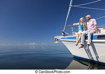 Happy Senior Couple on the Bow of a Sail Boat - A happy...
