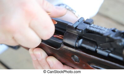 Loading a rifle. Shallow DOF. - Loading bullets into a...