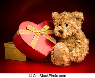 A Teddy Bear Hugging a Heart Shaped Box - A brown teddy bear...