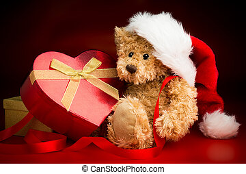 Teddy Bear Wearing a Christmas Hat and Hugging a Box - A...