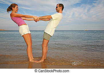 Man and woman stand on a beach