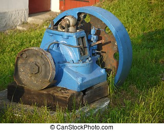 Old blue rusty engine laying in grass