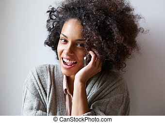 Happy young black woman talking on mobile phone - Close up...