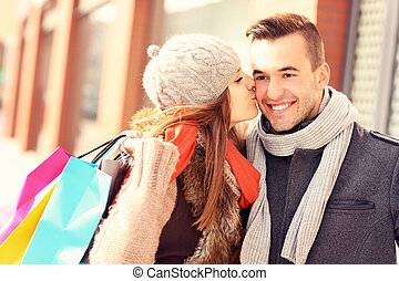 Happy woman kissing a man while shopping