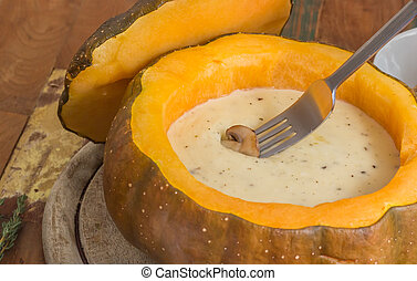 Cheese fondue in a roasted pumpkin with chestnut mushroom on...