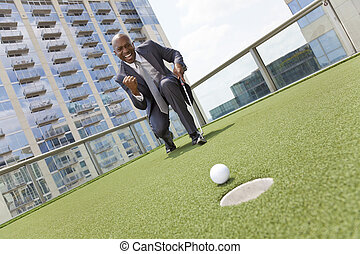 African American Businessman Playing Golf on Skyscraper...