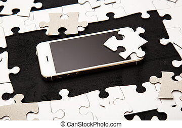 White puzzle with mobile phone on a black background
