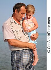 Grandfather holds granddaughter on hands at sea