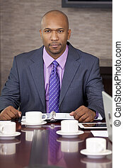 African AMerican Businessman Sitting in Office Boardroom -...