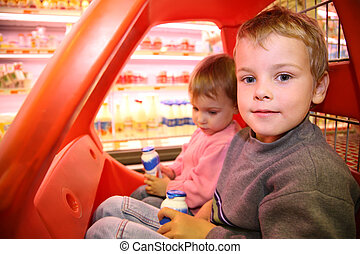 children in the toy automobile in the supermarket
