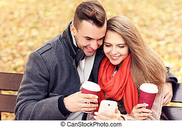 Young couple on a bench with smartphone in the park