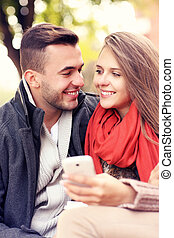 Joyful couple on a bench with smartphone in the park