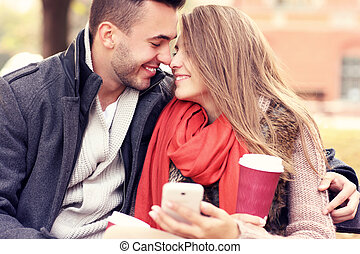 Romantic couple on a bench with smartphone in the park